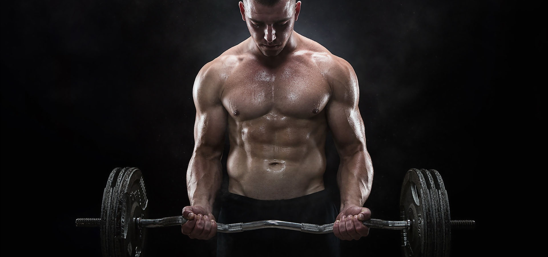 Man training in a gym with a barbell.